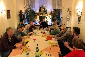 Aufnahme von schräg oben: Vorstandsmitglieder sitzen um großen Tisch und reden miteinander