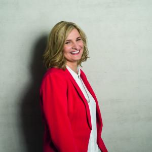 Kandidatinnenbild Cirsten Kunz (im roten Blazer vor grauem Hintergrund)